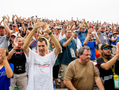 A crowd of applauding race fans.