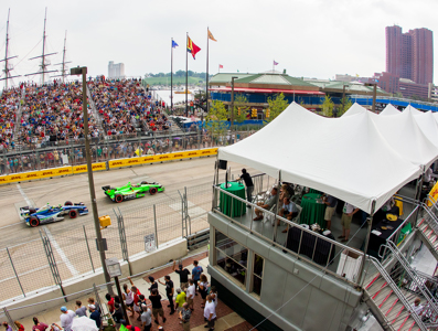 Vantage point view of cars on the track surrounded by crowds.