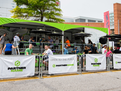 Covered outdoor seating area with sponsor signs covering the barriers.