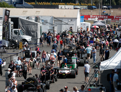 Parked race cars with crowds wandering amongst them.