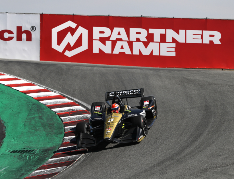 A car racing around a corner with a partner name banner on the side of the track.