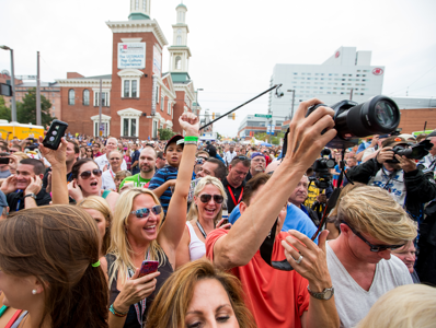 A large crowd in the street, many holding up cameras and phones.