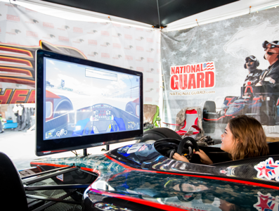 Someone in a mock racing car using a screen race simulator, with branding on the partition beside.
