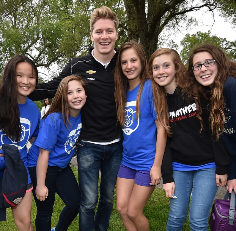 Group of young fans with an indy car driver